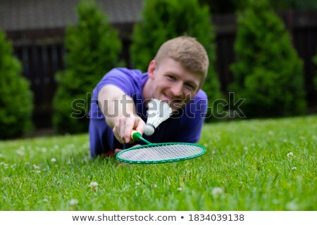 smiling young man with badminton rackets Stock photo © dolgachov