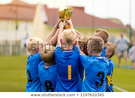 Young Athletes from School Sports Team Holding Winning Trophy Stock photo © matimix
