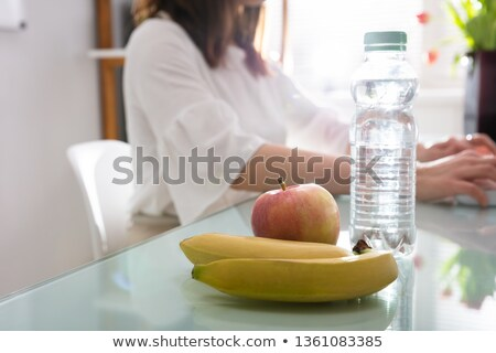 Apple, Banana And Water Bottle On Reflective Desk Stock photo © AndreyPopov