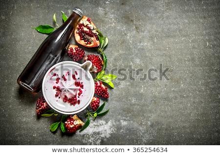 glass bottles of fruit juice on slate table top stock photo © dolgachov