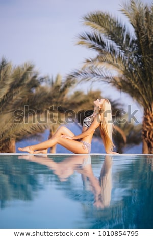 Woman lying on her back on pool edge sunbathing in her bikini Stock photo © boggy