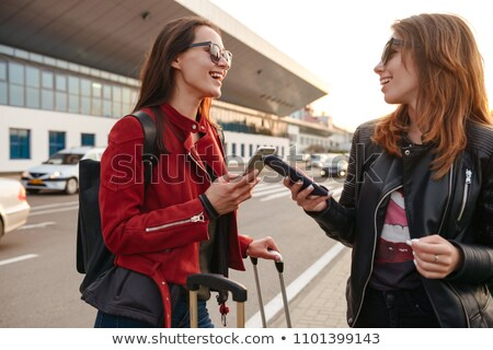 Photo of two excited european women traveling abroad, and using  Stock photo © deandrobot