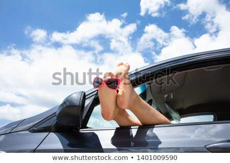 Sunglasses Over The Woman's Feet Out Of Car Window Stock photo © AndreyPopov