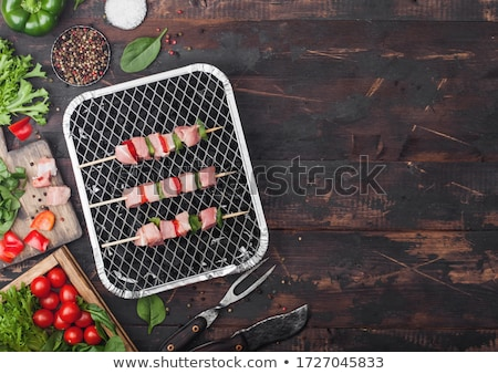 Stockfoto: Raw Pork Kebab With Paprika On Disposable Coal Bbq Grill With Fresh Vegetables On Wooden Background