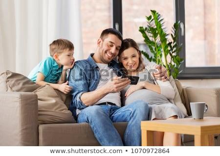 Incinta madre figlio smartphone home famiglia Foto d'archivio © dolgachov