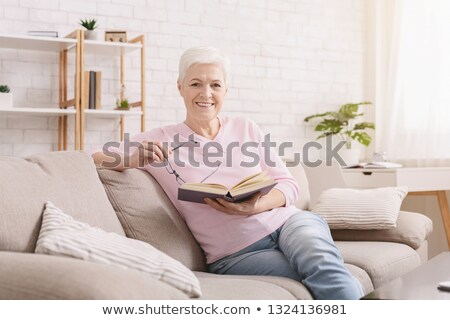 Cheerful senior woman sitting and reading a book stock photo © lichtmeister