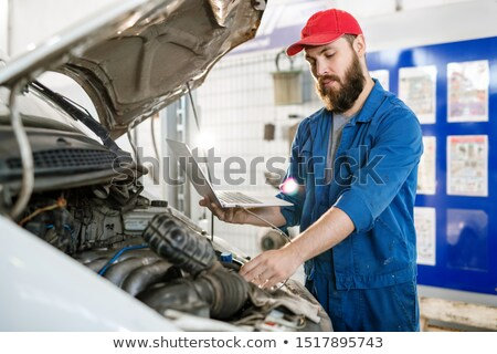 Serious young technician holding laptop and looking at details of engine Stock photo © pressmaster