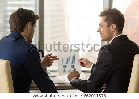 Two male analysts or economists pointing at documents with financial information Stock photo © pressmaster