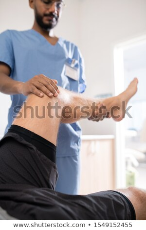 Contemporary medical specialist in uniform holding sick leg of his patient Stock photo © pressmaster