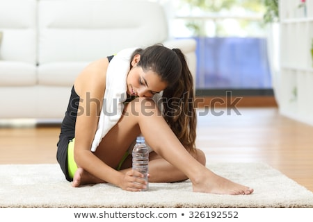 Thirsty young woman drinking water from bottle after workout at home Stock photo © pressmaster