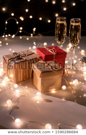 Three packed giftboxes, two flutes of champagne on table decorated with garlands Stock photo © pressmaster