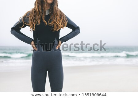 Mid section of young Caucasian woman standing with hands on hips on the beach. She wears surfsuit Stock photo © wavebreak_media