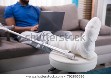 Man With Leg Injury Using Laptop Stock photo © AndreyPopov