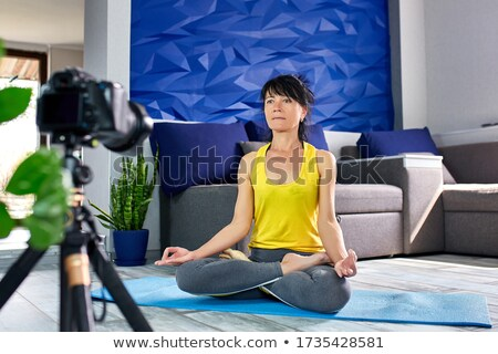 Blogger senior woman with slim body shape in sportswear doing yoga at home. Stock photo © Illia
