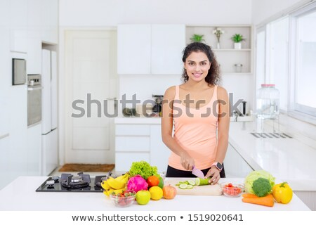 young woman holding paprika while cutting it Stock photo © Rob_Stark