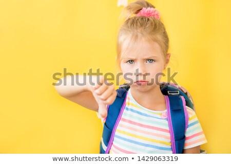 aggressive schoolgirl showing thumbs down stock photo © dolgachov