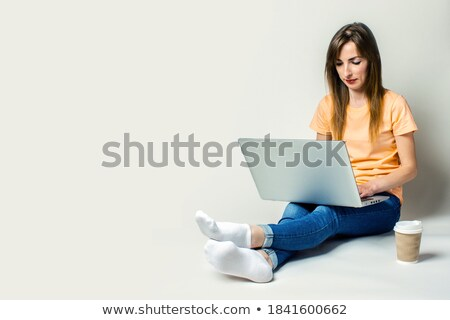 A smiling young woman holding a cup of coffee standing by her laptop stock photo © wavebreak_media