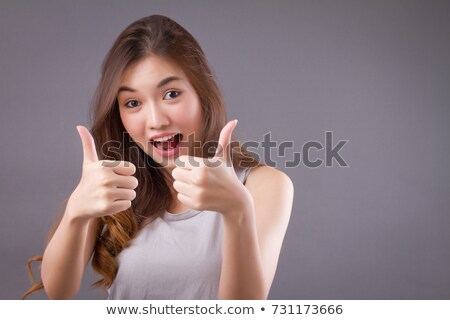 portrait of cheerful young woman gesturing double thumbs up stock photo © wavebreak_media