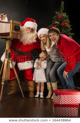 Santa Claus taking picture of full family with old wooden camera Stock photo © HASLOO