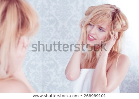 young smiling woman tousling hair in mirror stock photo © stryjek
