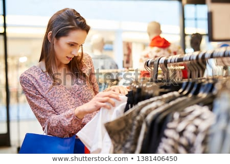 excited woman standing clothing shop stock photo © deandrobot