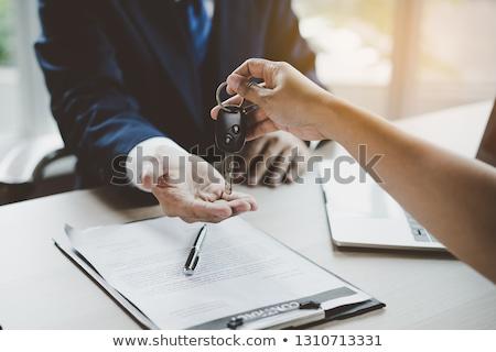 Businessman handing a key with paper agreement Stock photo © zurijeta