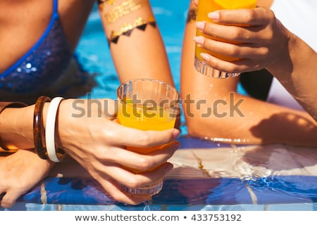 girlfriends clinking glasses with cocktails at the poolside  Stock photo © Yatsenko