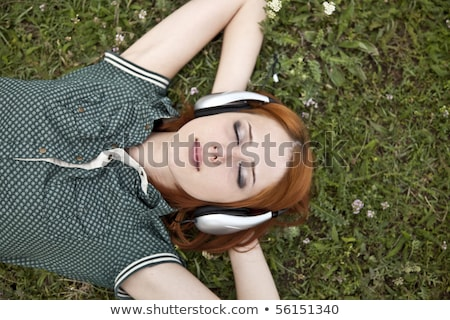 beautiful red haired girl at grass with headphones stock photo © massonforstock