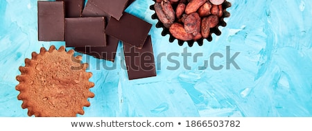 Cocoa beans background on blue table. Dark chocolate pieces Stock photo © Illia