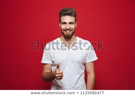 Portrait of a satisfied man standing over red background Stock photo © deandrobot