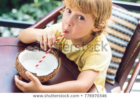 little boy drinks homemade coconut milk from a half of coconut stock photo © galitskaya