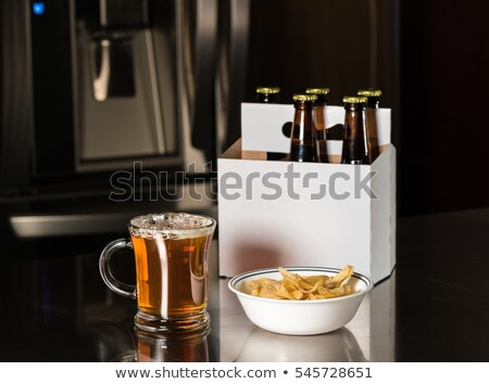 Beer in Bottle and Chips in Glass Bowl on Table Stock photo © robuart