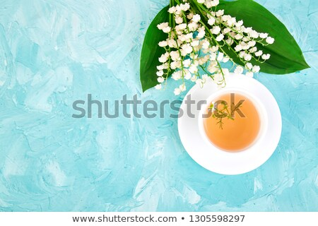 bouquet of lily of the valley and cup of chamomile tea stock photo © illia