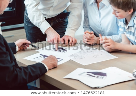 Family starting to plan a new kitchen in furnishing house Stock photo © Kzenon