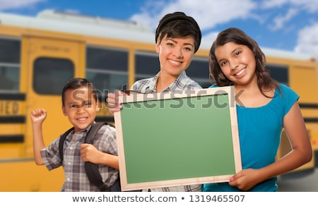 Young Mixed Race Students with Blank Chalkboard Near School Bus Stock photo © feverpitch