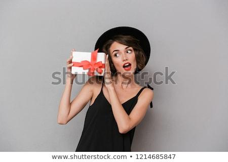 photo of gorgeous woman 20s wearing black dress holding gift box stock photo © deandrobot