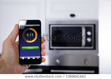 Person's Hand Operating Microwave Oven Application Stock photo © AndreyPopov