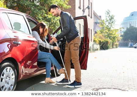 Husband Helping Her Disabled Wife To Get Inside The Car Stock photo © AndreyPopov
