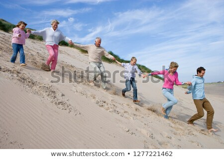 Young Man Running Down Sand Dune On Beach stock photo © monkey_business