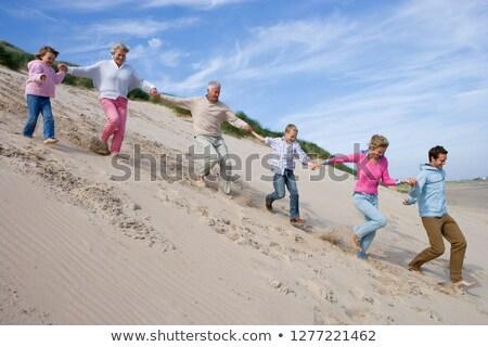 молодым человеком работает вниз песчаная дюна пляж человека Сток-фото © monkey_business