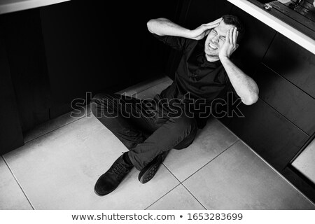 Frustrated man sits in the kitchen  Stock photo © Lopolo