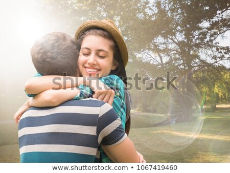 couple hugging in blurry park with flares stock photo © wavebreak_media