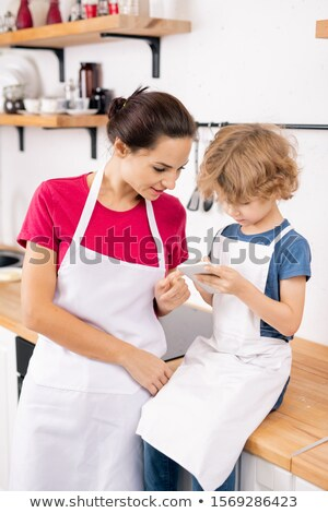 Cute little boy and his mother in aprons discussing ingredients of recipe Stock photo © pressmaster