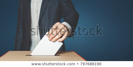 Voting concept with hand putting ballot into box Stock photo © vectorikart
