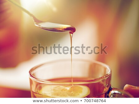 close up of woman adding sweetener to cup of tea Stock photo © dolgachov