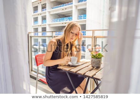 Young woman on the balcony annoyed by the building works outside. Noise concept. Air pollution from  Stock photo © galitskaya