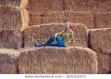 Farmer woman having break on bale of straw Stock photo © Kzenon