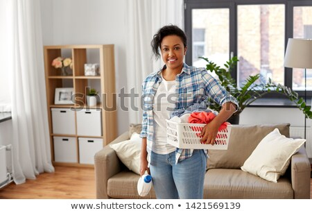 happy woman picking clothes for laundry at home Stock photo © dolgachov