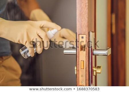 Coronovirus Prevention A man disinfects a doorknob. Closeup of a caucasian man disinfecting the door Stock photo © galitskaya