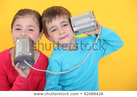 Stock fotó: Kids Having A Phone Call With Tin Cans On Yellow Background